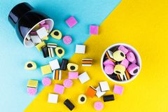Colorful liquorice allsorts spilling from a cup. Top view of colorful liquorice allsorts spilling from a cup Stock Photography