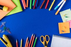Top view of colorful markers and pencils empty textbook and variety stationery. On blue background stock photos