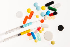 Top view of colorful medical pills and syringes on white Royalty Free Stock Photography