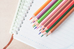 Top view of colorful pencil crayons on spiral notebook and green Stock Photos
