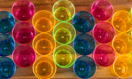 Top view of colorful red, blue, yellow cups on wooden surface Stock Image