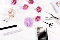 Top view of of colorful sea salt, towels, flowers, nail polishes, nail clippers, cuticle pusher, scissors, nail files and. Instruments for manicure at table in royalty free stock photo