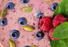 Top view of colorful smoothie cocktail as a background. Refreshing yogurt with ripe berries, seeds and mint leaves, close-up. Close-up of bright berry smoothie Stock Image