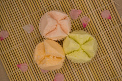 Top view of colorful Thai cupcake. On bamboo mat,decorated with pink flower petals Royalty Free Stock Photography