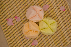 Top view of colorful Thai cupcake. On bamboo mat with pink flower petals Stock Images