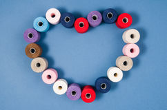 Top view of colorful thread spools over blue background Royalty Free Stock Images