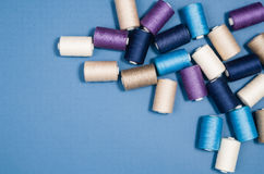 Top view of colorful thread spools over blue background Stock Image