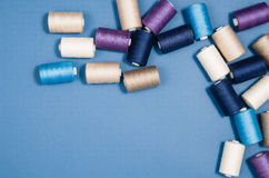 Top view of colorful thread spools over blue background Royalty Free Stock Photography