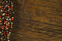 Rustic wooden desk and black table background with colour pepper royalty free stock photo