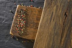 Rustic wooden desk and black table background with colour pepper stock photo