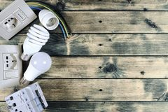 Top view of components for residential electrical installation on rustic wooden background. Close-up of components and elements for residential electrical Royalty Free Stock Image