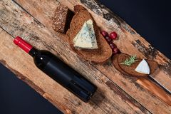Top view of composed bread slices with blue cheese and grapes on wooden planks with bottle of wine.  royalty free stock photo