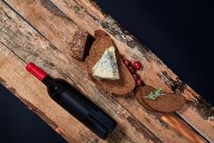 Top view of composed bread slices with blue cheese and grapes on wooden planks with bottle of wine.  royalty free stock photos