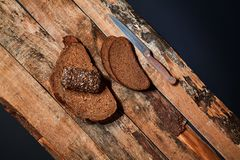 Top view of composed slices of black bread on wooden planks with. Knife above black background royalty free stock image