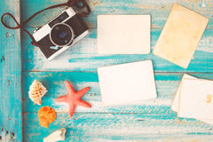Top view composition - Blank paper photo frames with starfish, shells, coral and items on wooden table Stock Images