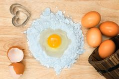 Top view composition flour with egg and ingredients for homemade bakery on wooden background.  Stock Image
