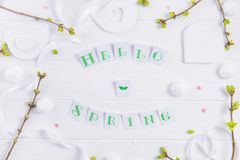 Top view composition of Hello spring lettering, branches with young shoots of greenery, merengue sweets and candy hearts, handcraf. T bird figure on wooden Royalty Free Stock Photography