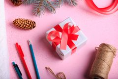 Top view of Christmas gift making. Present box and crafting decorations on a pink table background. stock photo