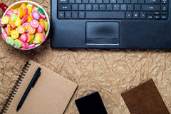 Top view of a computer, laptop, candy, notebook, pen, smartphone stock images