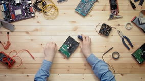 Top view computer technician repairing hard drive at wooden desk with tools and electronic components