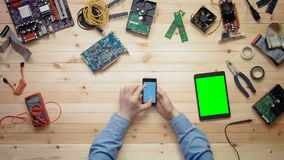 Top view computer technician using smart phone with circuit board outline and digital tablet with green screen lying at stock video footage