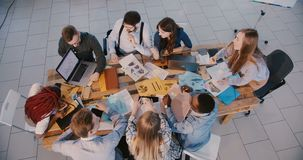 Top view concept of teamwork, multiethnic business people working together analysing financial data in modern office.