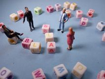 Top View Conceptual / Illustration Chit Chat, Alphabet Plastic Cube Beads Beyond 3 Miniature Figure Businessman and 1. Businesswoman at Blue Background or Floor royalty free stock image