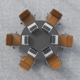 Top view of a conference room. A black round table, six brown leather chairs and six laptops. Office interior. Royalty Free Stock Photos