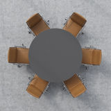 Top view of a conference room. A dark grey round table and six brown leather chairs around. 3D interior. Stock Photos