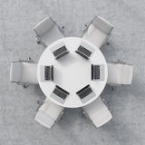 Top view of a conference room. A white round table, six chairs. Six laptops are on the table. Office interior. Royalty Free Stock Image
