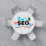 Top View of a conference room. A white round table and six white chairs around. Colourful SEO flowchart is drawn on the table surf Stock Photography