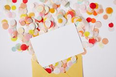 Top view of confetti pieces, white paper and yellow envelope on white surface royalty free stock photography