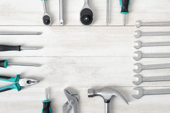 Top view of construction tools including hammer and different sized screwdrivers, wrenches on wooden surface with open Stock Images