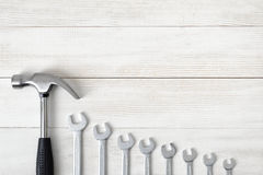 Top view of construction tools including hammer and different sized wrenches on wooden surface with open space. Stock Photo