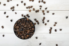 Top view of container for coffee with scattered beans on wooden surface Royalty Free Stock Photography