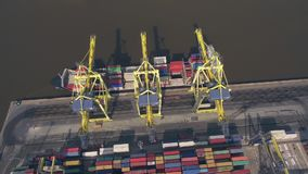 Top view of container ship unloading in port. Aerial view of cargo ship unloading in container terminal stock video