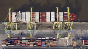 Top view of container ship unloading in port. Aerial view of cargo ship unloading in container terminal stock video footage