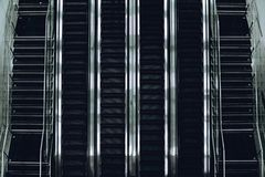 Escalator lines in modern deport. Top view of contemporary glass and chrome escalator line of four tracks with two stairways on both sides in airport terminal Royalty Free Stock Photo
