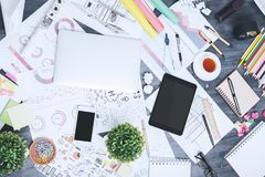 Contemporary messy workspace. Top view of contemporary messy workspace with various, supplies, devices and sketches. Close up Royalty Free Stock Photo
