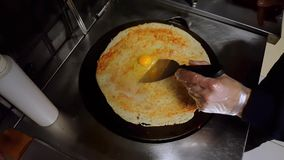 Cook cracking an egg on crepe on a black cooker. Top view of a cook cracking an egg on crepe on a black cooker for preparation stock footage