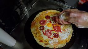 Cook preparing a crepe with cheese, Turkish sauge (sucuk) and egg stock video