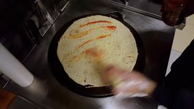 Cook putting some tomato sauce on crepe on a black cooker. Top view of a cook putting some tomato sauce on crepe on a black cooker for preparation stock video