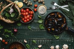 Top view of cooked mussels with shells served in pan with tomatoes, herbs and wine. On rustic table Stock Images