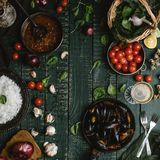 Top view of cooked mussels with shells served in pan with tomatoes, herbs and wine. On wooden table Stock Images