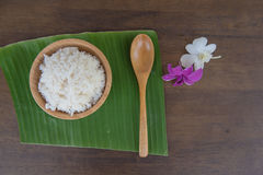 Top view Cooked rice in bowl on green banana leaf spoon and orchid . Stock Photo