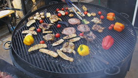 Top View of the Cooking of Meat and Vegetables on the Grill. Hand Using Tongs For Turning Meat on the Barbecue. Sausages, chicken, bell pepper, eggplant stock footage