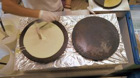 Making crepes in street snack bar. Top view of cooking in snack bar. Cook pouring dough onto the stove and making a crepe stock video footage