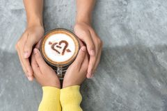 Top view with copy space. Couple in love holding hands with coffee love on table. stock photography