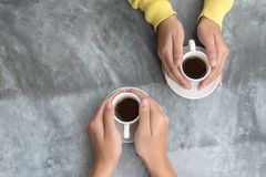 Top view with copy space. Couple in love holding hands with coffee love on table. royalty free stock images