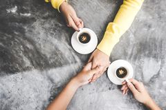 Top view with copy space. Couple in love holding hands with coffee love on table. royalty free stock image